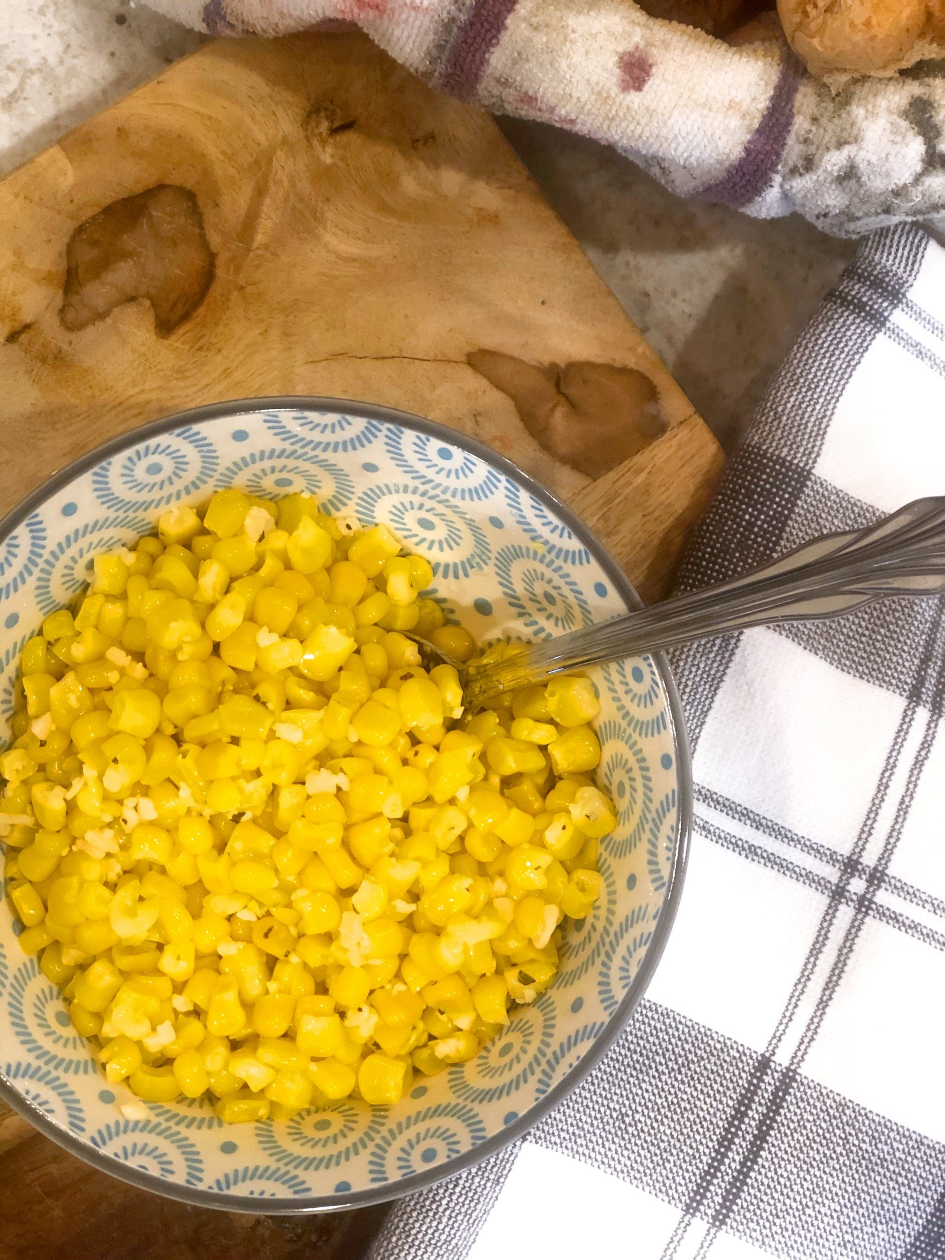 birdseye view of a bowl of corn on a wooden board next to a plaid towel