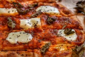 close up of crispy naan pizza with melted mozzarella cheese on tomato sauce topped with fresh basil