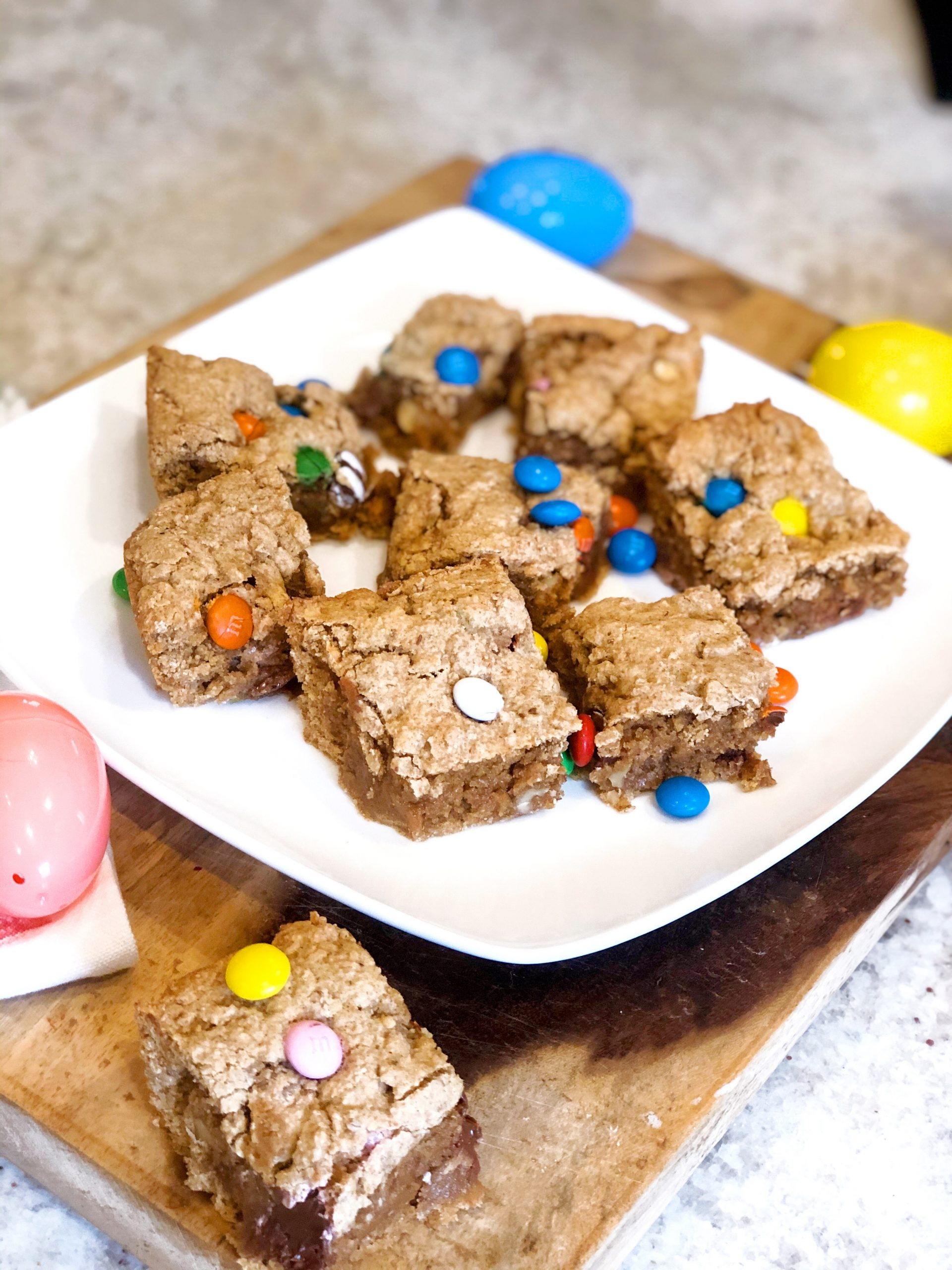 healthy blondies with m & m's on a white plate surrounded by Easter eggs