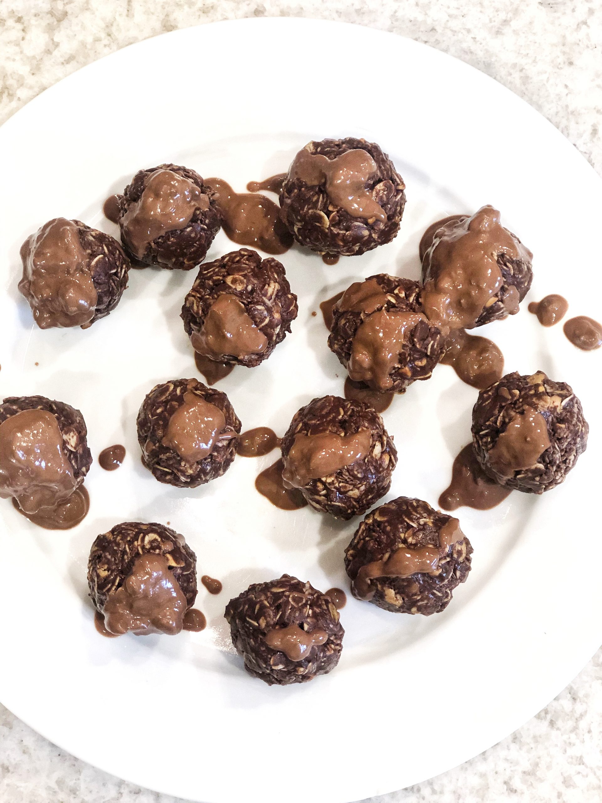 no bake chocolate oat bites on a white plate drizzled in melted chocolate