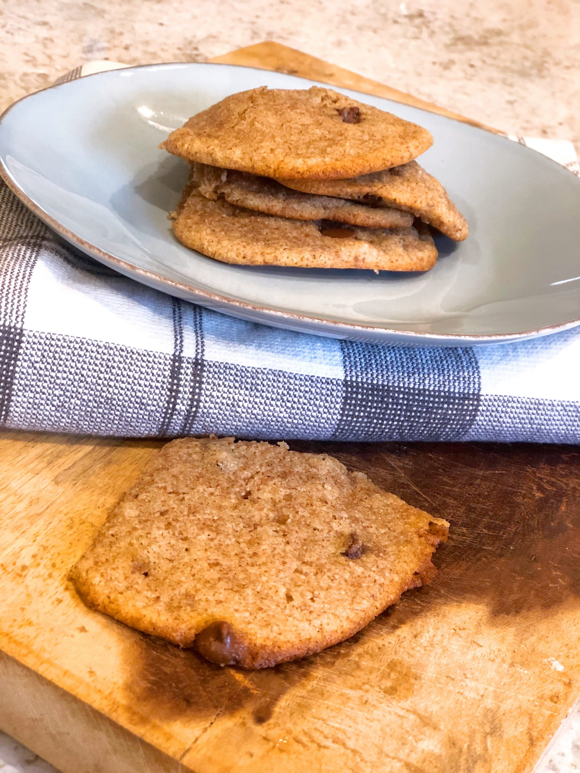 almond cookies on a blue plate sitting on a white cloth on a wooden board