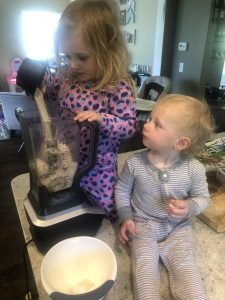 little boy and girl adding ingredients to the blender