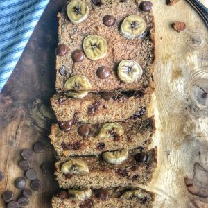 flourless banana bread on a wooden board with chocolate chips and banana slices on top