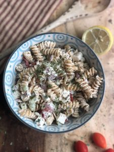 creamy cucumber tomato and chickpea pasta salad in a blue bowl on a wooden board