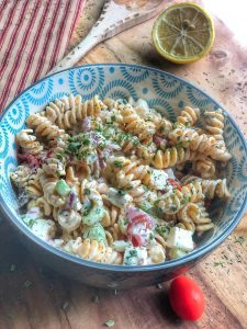 close up of creamy cucumber tomato and chickpea pasta salad in a blue bowl on a wooden board