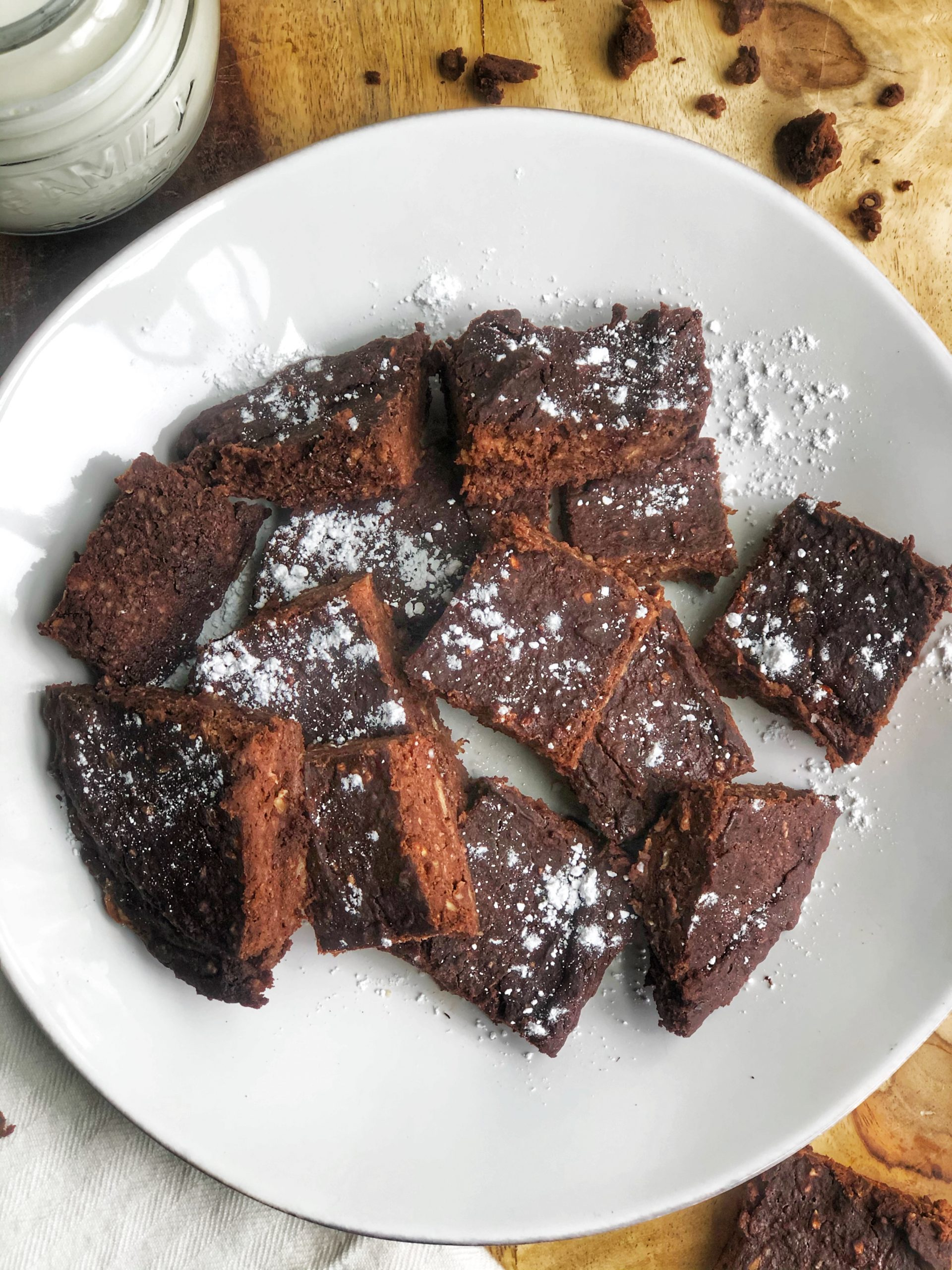 flourless fudgy brownies on a white plate with powdered sugar on top