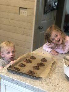 little blonde children helping to make peanut butter chocolate chip cookies