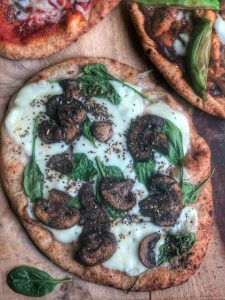 spinach mushroom and cheese naan pizza on a wooden board