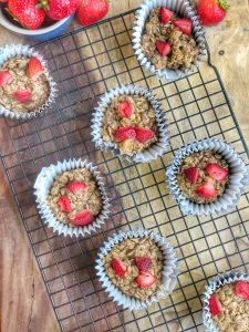 peanut butter and jelly oatmeal cups on a cooling rack with strawberries all around