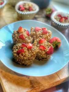 close up of peanut butter and jelly oatmeal cups on a blue plate with strawberries in a small bowl
