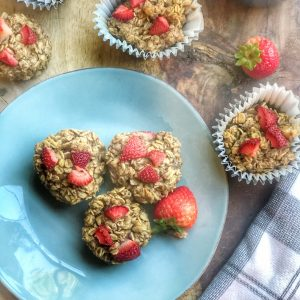 peanut butter and jelly oatmeal cups on a blue plate with strawberries all around