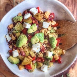 avocado tomato and mozzarella salad in a white bowl on a wooden board