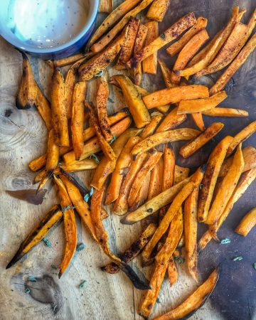 the crispiest sweet potato fries on a wooden board with ranch dressing on the side