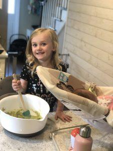 little blonde girl mixing matcha muffins