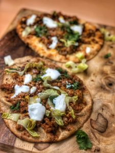 taco naan pizza on a wooden cutting board