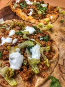 close up of taco naan pizza on a cutting board