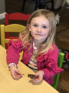 little blonde toddler eating brownies wearing a pink jacket