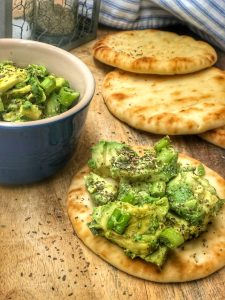 close up of avocado and scallion salsa on a piece of mini naan bread on a cutting board