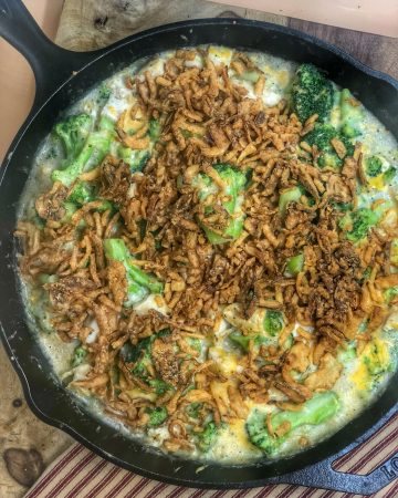 chicken and broccoli casserole in a cast iron skillet on a wooden cutting board