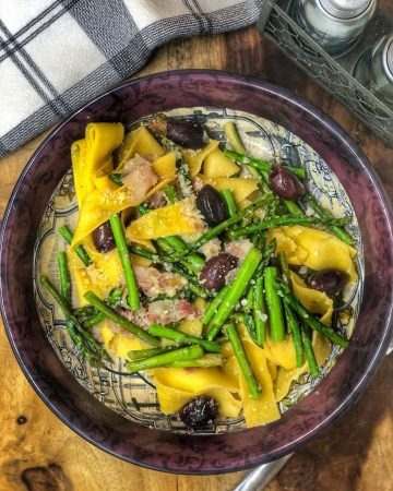 asparagus olives and pancetta paparradelle in a maroon bowl on a wooden board