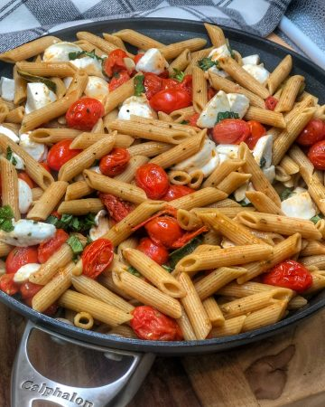 cherry tomato and garlic penne in a non-stick skillet sitting on a wooden cutting board