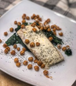 roasted mahi mahi and chickpeas over spinach on a white plate on a wooden board