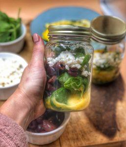 a hand holding a breakfast jar with a greek omelette inside