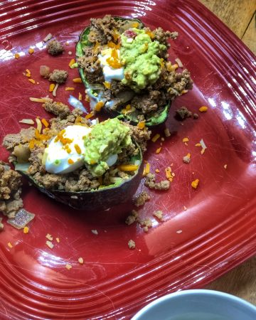 side view of stuffed avocado tacos with ground turkey and sour cream and a side of guacamole