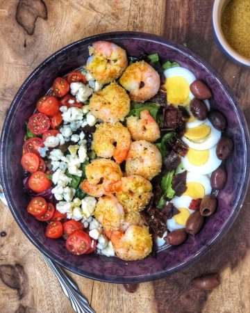 birds eye view of shrimp cobb salad in a maroon bowl with tomatoes, blue cheese, eggs, and olives