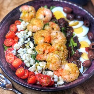 shrimp cobb salad in a maroon bowl with tomatoes blue cheese eggs and olives