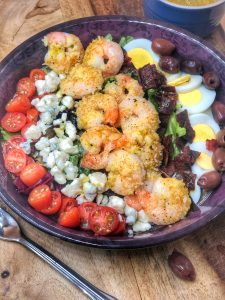 shrimp cobb salad in a maroon bowl with tomatoes, blue cheese, eggs, and olives
