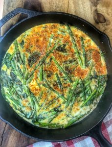 green frittata in a cast iron skillet on a wooden cutting board