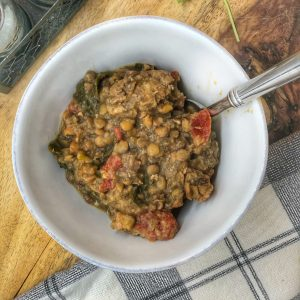 slow cooker lentil soup in a white bowl with a silver spoon on a wooden cutting board