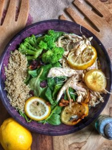 roasted lemon chicken with broccoli and quinoa on a wooden board