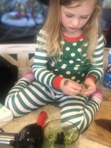 blonde girl in green and white pajamas using a hand mixer to help chop broccoli