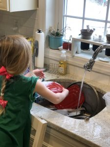 blonde girl doing the dishes with a pink bow in her hair