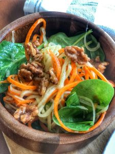 close up of spiralized zucchini and carrots mixed with spinach and walnuts