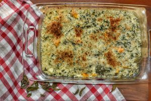 birds eye view of cheesy squash gratin in a glass baking dish on a red and white checkered napkin