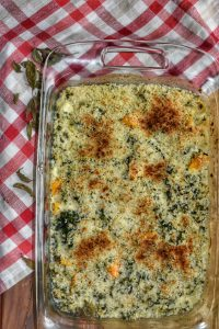 cheesy squash gratin in a glass baking dish on a red and white checkered napkin
