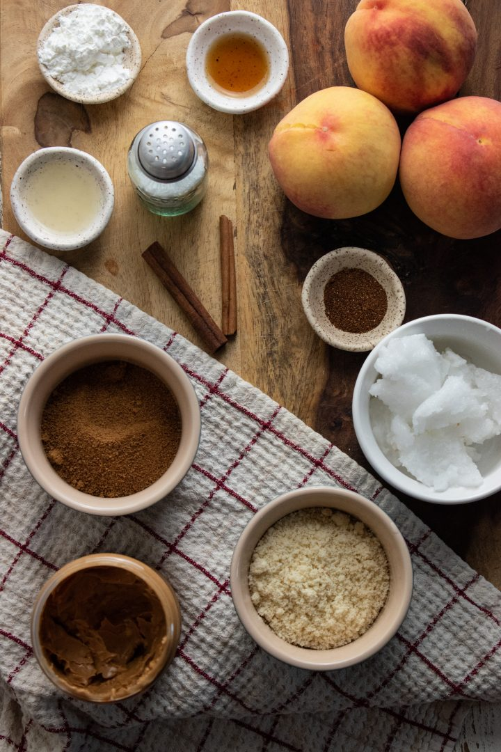 healthy peach crispy ingredients laid out on a wooden cutting board