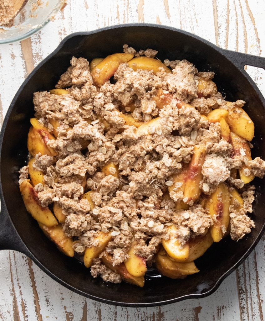 healthy peach crisp in a cast iron skillet right before baking