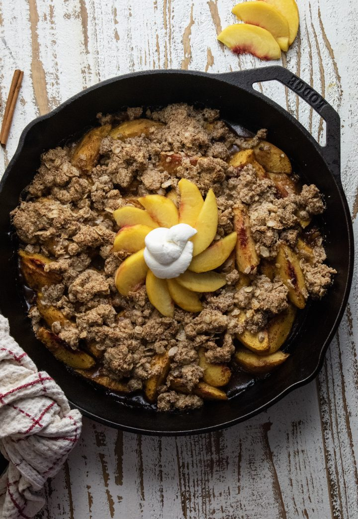 healthy peach crisp topped with more sliced peaches in a circle and topped with homemade keto whipped cream