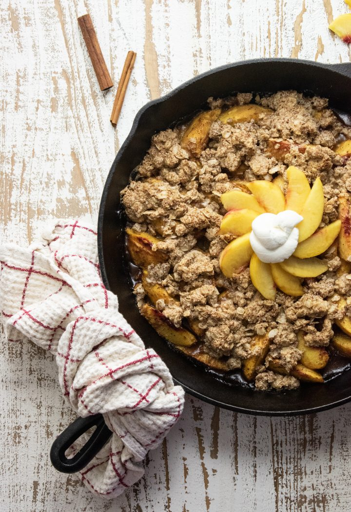 healthy peach crisp in a cast iron skillet on a white wooden cutting board