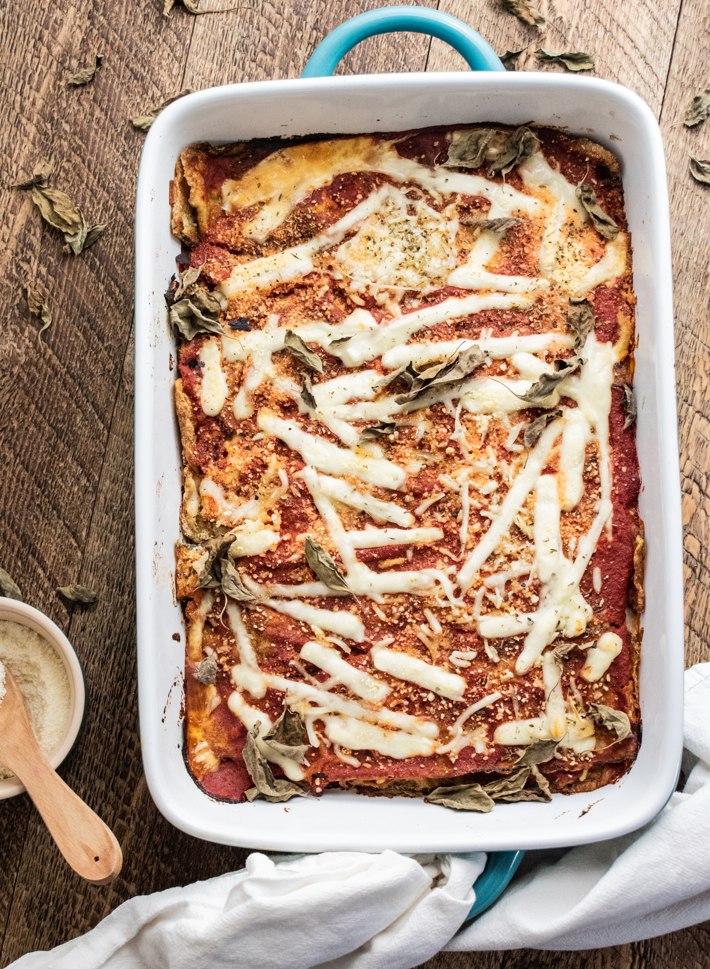 birds eye view of zucchini parmesan in a blue 9 x 13 inch baking dish on a wooden table